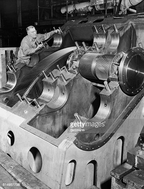 Gleaming wheels gears and bearing seats are 'lined up' prior to a test run of the main propulsion unit for the USS Saratoga Built with the precision...