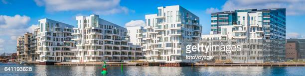 Gleaming white modern apartment buildings waterfront homes panorama Copenhagen Denmark