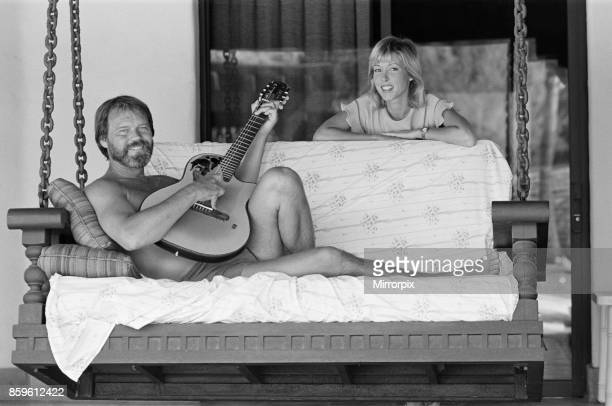 Glen Campbell and his wife to be Kim Woollen at home in Phoenix Arizona USA Glen serenades Kim singing songs with his guitar by the swimming pool...