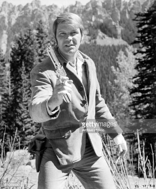 Glen Campbell holds a gun in a scene from the film 'True Grit' 1969