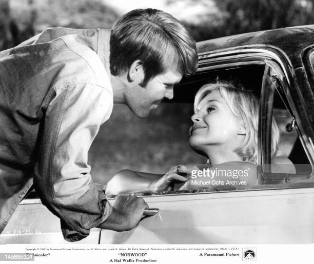 Glen Campbell leaning in to see Carol Lynley sitting in an automobile as she stares at him with flirtatious eyes in a scene from the film 'Norwood'...