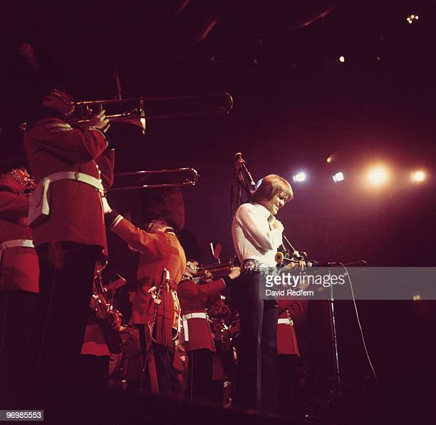 Glen Campbell performs on stage with a British military band at the Royal Albert Hall in London England in 1977
