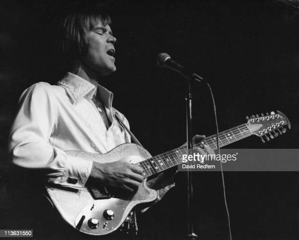 Glen Campbell, U.S. Country music singer, playing the guitar and singing into a microphone during a live concert performance at the Royal Albert...