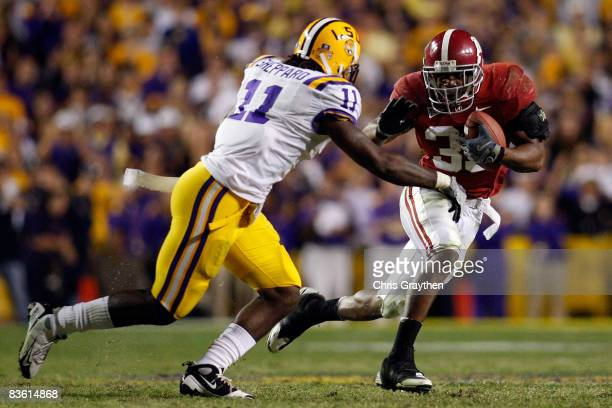 Glen Coffee of the Alabama Crimson Tide tries to avoid a tackle by Kelvin Sheppard of the Louisiana State University Tigers on November 11 2008 at...