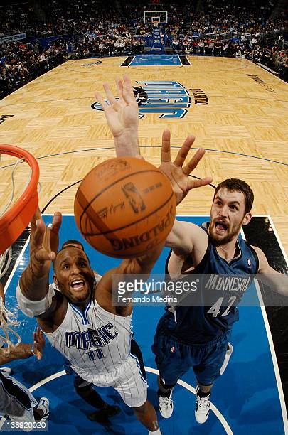 Glen Davis of the Orlando Magic and Kevin Love of the Minnesota Timberwolves reach for a rebound during the game on February 13 2012 at Amway Center...