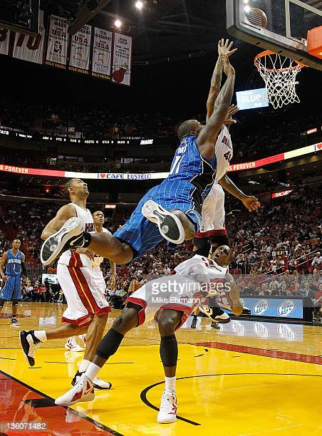 Glen Davis of the Orlando Magic commits a charge against Mario Chalmers of the Miami Heat during a preseason game at AmericanAirlines Arena on...