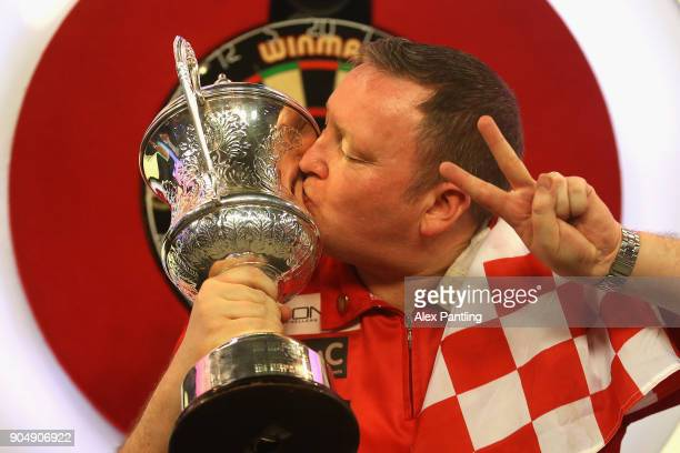 Glen Durrant of England celebrates victory as he kisses the trophy following the final of the BDO World Darts Championship against Mark McGeeney of...