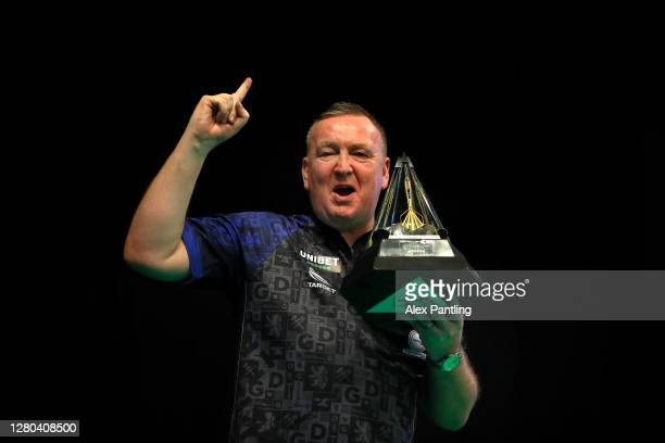 Glen Durrant of England celebrates victory with the trophy after his final against Nathan Aspinall of England during the Unibet Premier League...