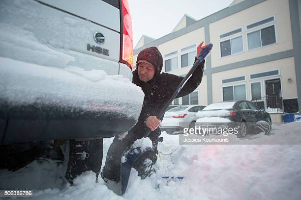 Glen Eck attempts to put chains on his tire while his car is stuck in a snow drift on January 23 2016 in Philadelphia Pennsylvania The city is under...