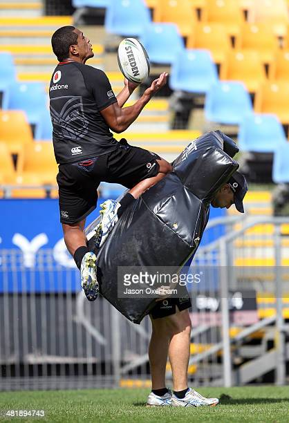 Glen Fisiiahi of the Warriors takes a high ball with Warriors assistant coach Andrew McFadden holdin the pads during a New Zealand Warriors NRL...