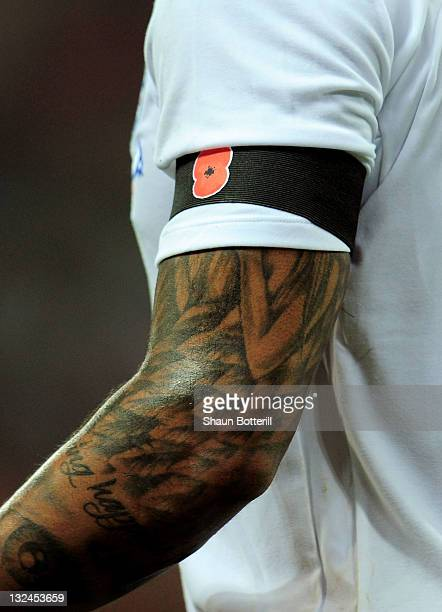 Glen Johnson of England displays a poppy on an armband during the international friendly match between England and Spain at Wembley Stadium on...