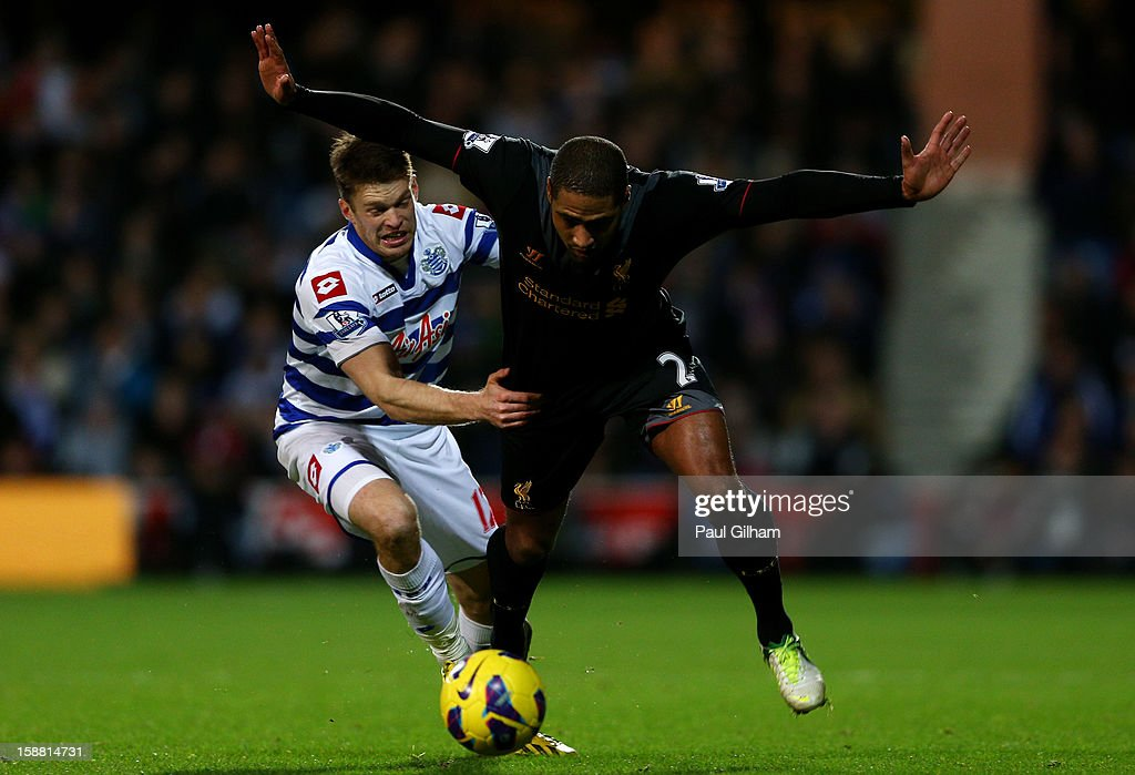 Glen Johnson of Liverpool attempts to hold off the challenge from Jamie Mackie of QPR during the Barclays Premier League match between Queens Park Rangers and Liverpool at Loftus Road on December 30, 2012 in London, England.