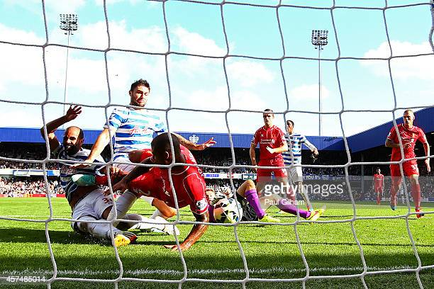 Glen Johnson of Liverpool blocks an attempt from Sandro and Charlie Austin of QPR during the Barclays Premier League match between Queens Park...