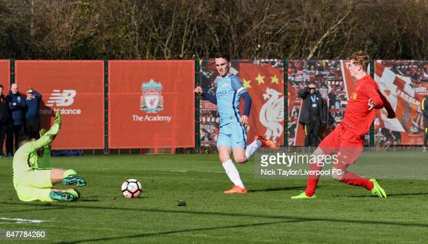 Glen McAuley of Liverpool and goalkeeper Arijanet Muric of Manchester City in action during the U18 Premier League match between Liverpool and...