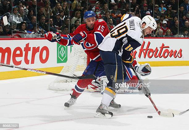Glen Metropolit of the Montreal Canadiens defends against Tim Connolly of the Buffalo Sabres as he controls the puck at the Bell Centre on March 28...
