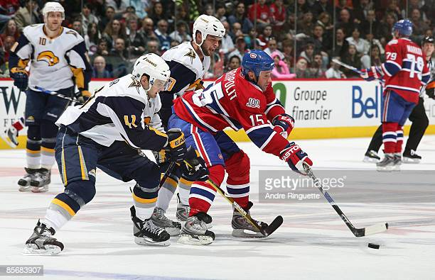 Glen Metropolit of the Montreal Canadiens stickhandles the puck against Clarke MacArthur and Tim Connolly of the Buffalo Sabres at the Bell Centre on...