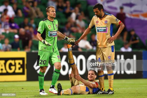 Glen Moss and Nikolai ToporStanley of the Jets assist Nigel Boogaard with cramp during the round 10 ALeague match between the Perth Glory and the...