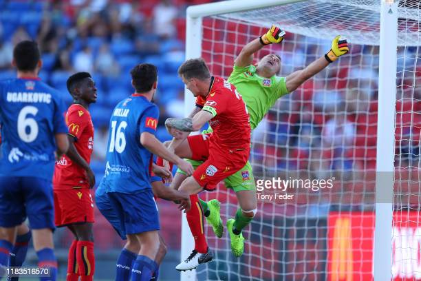 Glen Moss of the Newcastle Jets attempts a save against Michael Jakobsen of Adelaide United during the round three A-League match between the...