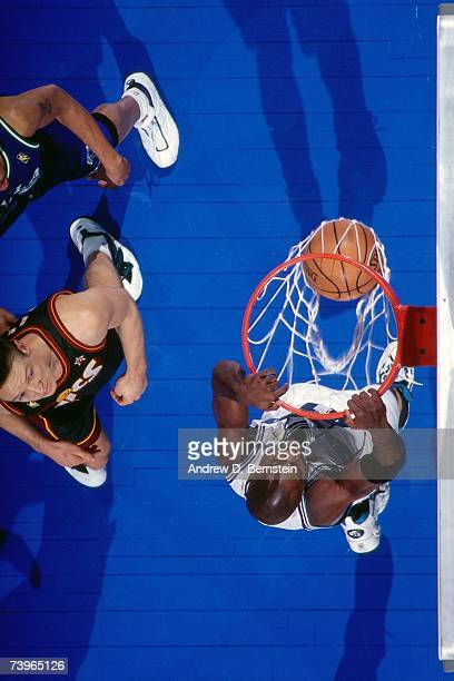 Glen Rice of the Eastern Conference dunks against Detlef Schrempf the Western Conference during the 1997 AllStar Game on February 9 1997 at Gund...