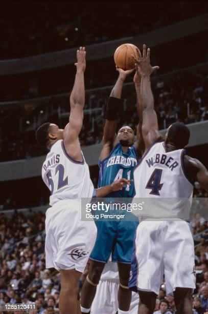 Glen Rice, Small Forward for the Charlotte Hornets shoots for the basket as Chris Webber and Terry Davis of the Washington Wizards attempt to block...