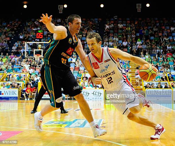 Glen Saville of the Hawks drives past Stephen Hoare of the Crocodiles during game two of the NBL semi final series between the Townsville Crocodiles...