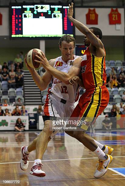 Glen Saville of the Hawks is challenged by Bennie Lewis of the Tigers during the round four NBL match between the Melbourne Tigers and the Wollongong...