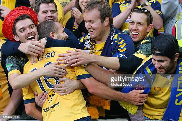 Glen Trifiro of Central Coast Mariners is mobbed by fans after they drew the game with a late goal during the round six ALeague match between...