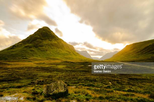 glencoe valley during golden hour sunset in a partly cloudy summer day, sunbeam through the clouds. green grass everywhere. mountains in the background - hill stock pictures, royalty-free photos & images