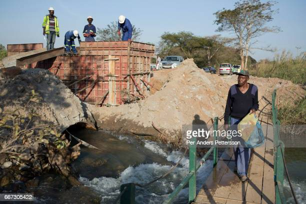 Glencore contractors construct a small bridge that collapsed and stranded people between villages and Mufilira on July 6 2016 Glencore an AngloSwiss...