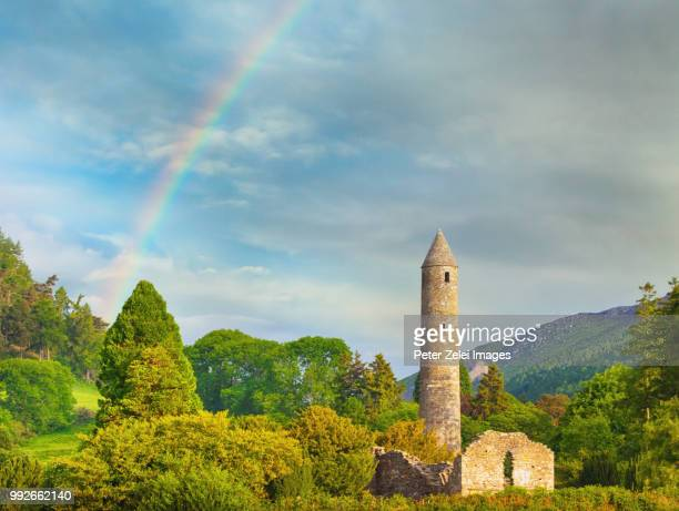 glendalough monastic site in ireland with a rainbow - irish round tower stock photos and pictures