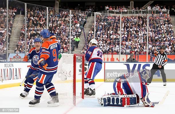 Glenn Anderson and Craig Simpson of the Edmonton Oilers alumni celebrate after a goal on Bob Essensa of the Winnipeg Jets alumni during the 2016 Tim...