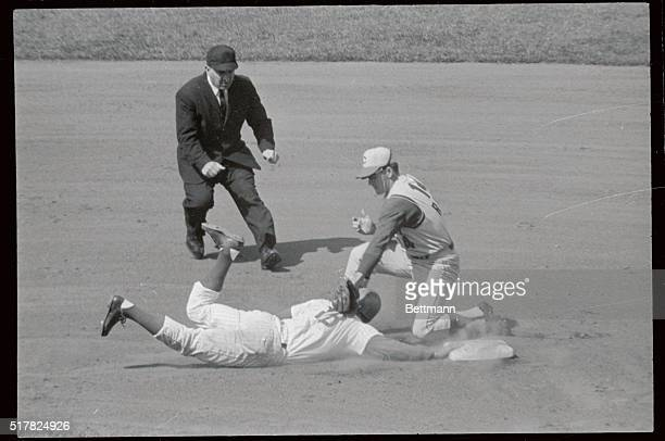 Glenn Beckert of the Cubs makes head first dive back to 2nd base just in time as Cincinnati Reds 2nd baseman Pete Rose attempts tag in 1st inning of...