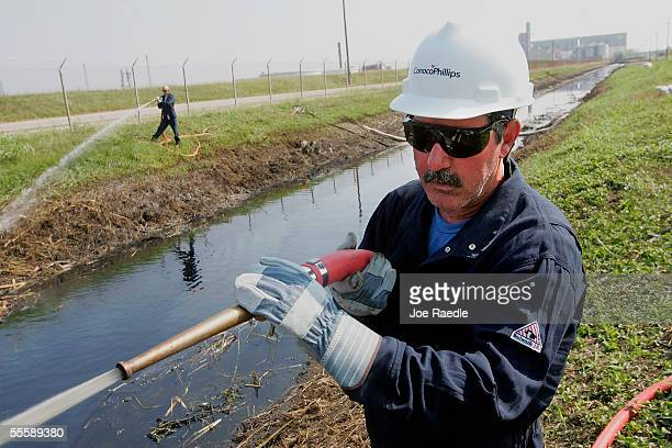 Glenn Bratton who is working for Oil Mop Inc sprays water in a canal to push crude oil towards a skimmer to extract the oil that came from the...