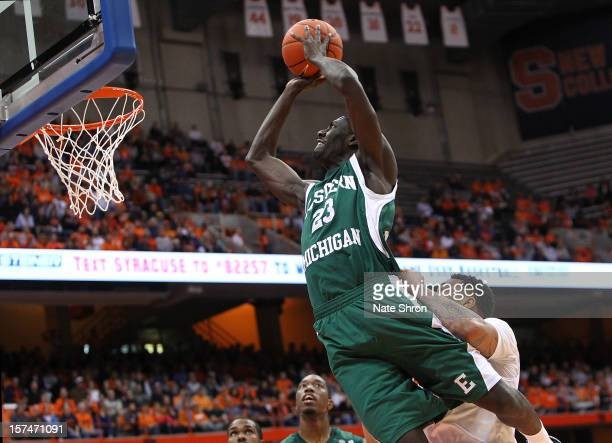 Glenn Bryant of the Eastern Michigan Eagles shoots the ball as he is pulled down by DaJuan Coleman of the Syracuse Orange during the game at the...