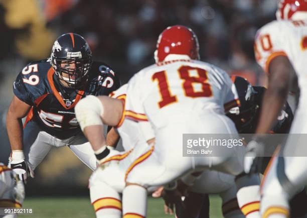 Glenn Cadrez Linebacker for the Denver Broncos keeps his eyes on Elvis Grbac Quarterback for the Kansas City Chiefs as he prepares to snap the ball...