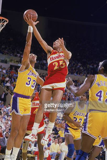 Glenn Doc Rivers of the Atlanta Hawks shoots over Kareem AbdulJabbar of the Los Angeles Lakers during a NBA game at the Great Western Forum in...