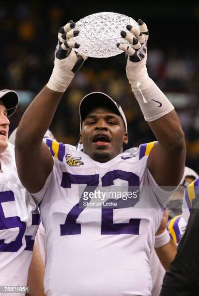 Glenn Dorsey of the Louisiana State University Tigers raises the trophy after defeating the Ohio State Buckeyes 38-24 in the AllState BCS National...