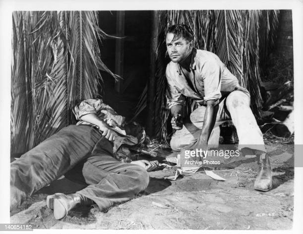 Glenn Ford is a desperate man of action as he stoops beside the prone form of Rico Alaniz in a scene from the film 'Appointment In Honduras' 1953