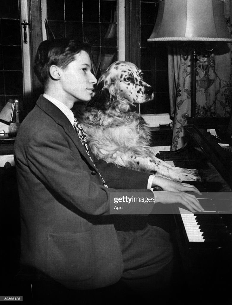 Glenn Gould (1932-1982), 15 years old, playing the piano at home with his dog Nickey, in 1947 : News Photo