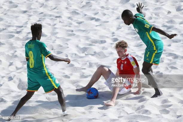 Glenn Hodel of Switzerland is challenged by Hamad Diouf and Papa Ndour of Senegal during the FIFA Beach Soccer World Cup Bahamas 2017 group A match...