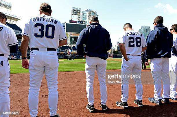 Glenn Hoffman Bud Black and Phil Plantier of the San Diego Padres participate in a moment of silence during a pre game video honoring the late San...