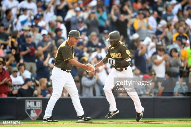 Glenn Hoffman congratulates Manuel Margot of the San Diego Padres after hitting his second home run of the game on Opening Day against the San...