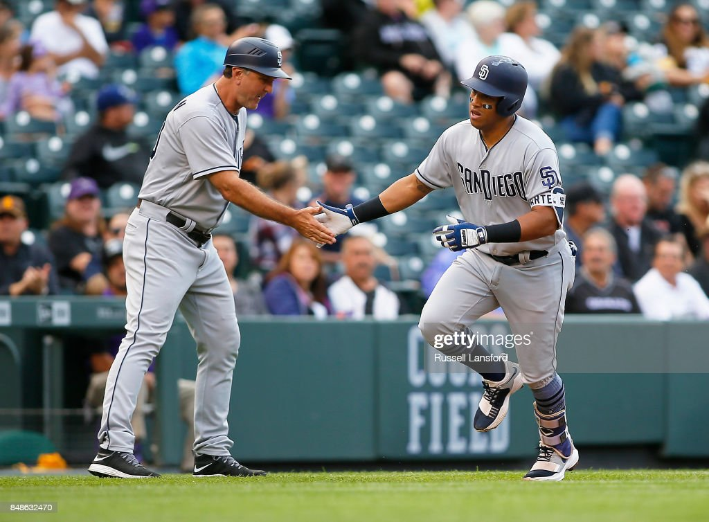 Glenn Hoffman #30 of the San Diego Padres congratulates Yangervis Solarte #26 following a solo homerun in the sixth inning of a regular season MLB game between the Colorado Rockies and the visiting San Diego Padres at Coors Field on September 17, 2017 in Denver, Colorado.