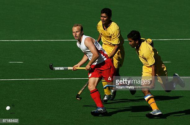 Glenn Kirkham of England breaks between Kali Logan Raj and Kali Keevan Raj of Malaysia in the Men's Bronze Medal match during the hockey at the...