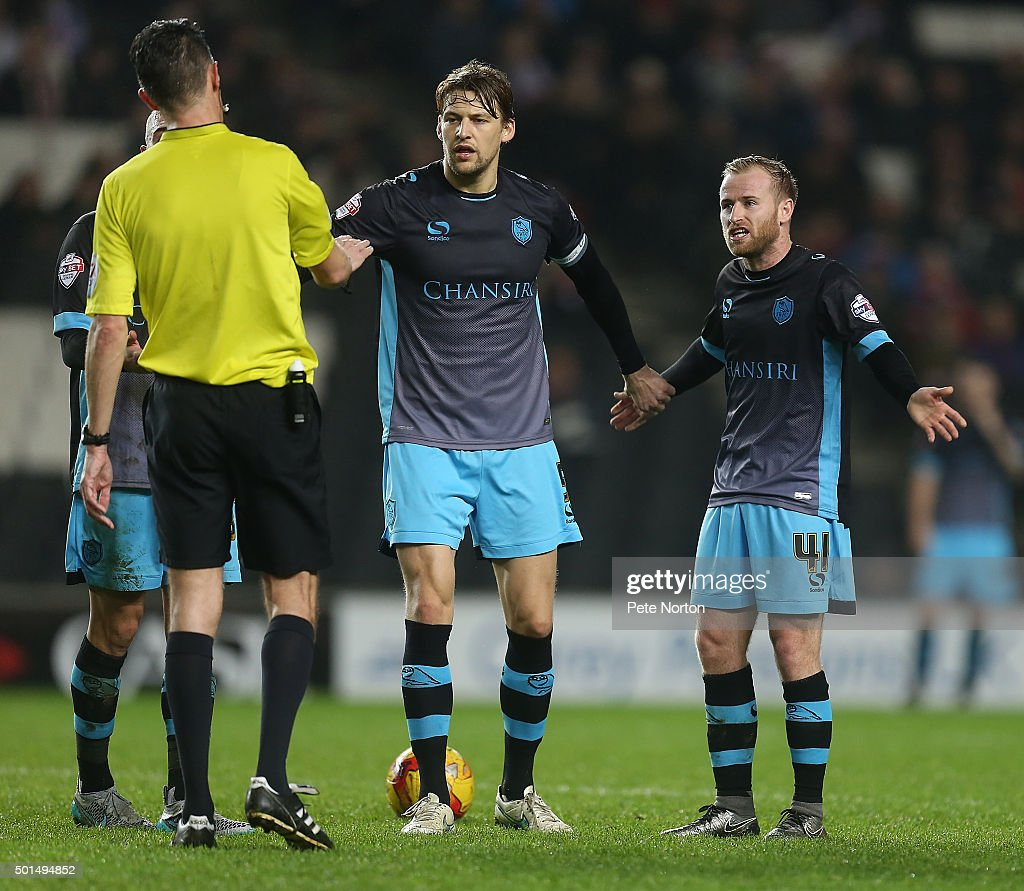 Glenn Loovens and Barry Bannan of Sheffield Wednesday remonstrate with referee Darren Deadman during the Sky Bet Championship match between Milton Keynes Dons and Sheffield Wednesday at stadium:mk on December 15, 2015 in Milton Keynes, United Kingdom.