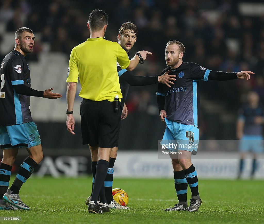 Glenn Loovens, Jack Hunt and Barry Bannan of Sheffield Wednesday remonstrate with referee Darren Deadman during the Sky Bet Championship match between Milton Keynes Dons and Sheffield Wednesday at stadium:mk on December 15, 2015 in Milton Keynes, United Kingdom.