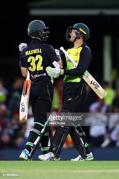 Glenn Maxwell and Alex Carey of Australia celebrate victory during game one of the International Twenty20 series between Australia and New Zealand at...