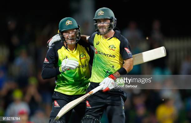 Glenn Maxwell of Australia celebrates his century with Alex Carey after hitting a six from the last ball during the Twenty20 International match...