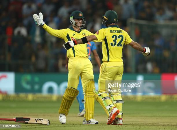Glenn Maxwell of Australia celebrates scoring the winning runs with Peter Handscomb during game two of the T20I Series between India and Australia at...