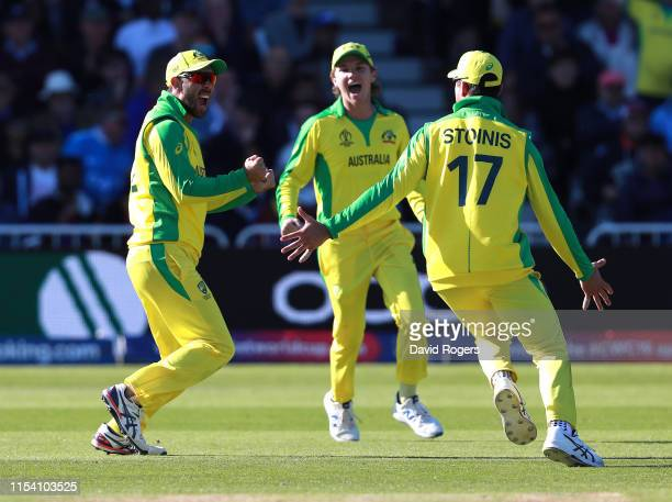 Glenn Maxwell of Australia celebrates with team mates Marcus Stoinis and Adam Zampa after catching Andre Russell during the Group Stage match of the...